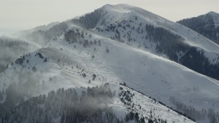 AX125_181 - 6K stock footage aerial video of snowdrifts on peaks in the Oquirrh Mountains in winter, Utah