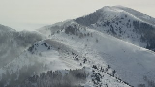 AX125_182 - 6K stock footage aerial video snowdrift plumes from peaks in the Oquirrh Mountains, Utah