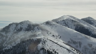 AX125_184 - 6K stock footage aerial video of Oquirrh Mountains peaks with winter snowdrifts in Utah