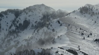 AX125_185 - 6K stock footage aerial video of Oquirrh Mountains with snowdrifts in wintertime, Utah