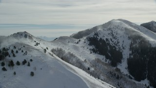 AX125_192 - 6K stock footage aerial video of two peaks with snowdrifts in the Oquirrh Mountains or Utah in winter