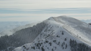 AX125_195 - 6K stock footage aerial video approach snowy mountain peak with winter snowdrifts, Oquirrh Mountains, Utah