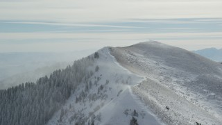 AX125_196 - 6K stock footage aerial video of approaching snowdrifts blowing off mountain peak in winter, Oquirrh Mountains, Utah