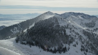 AX125_199 - 6K stock footage aerial video of snowdrifts pluming from a mountain peak in wintertime in Utah's Oquirrh Mountains