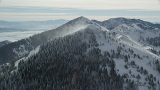 AX125_200 - 6K stock footage aerial video of approaching snowdrifts from the summit of a wintery mountain peak, Oquirrh Mountains, Utah