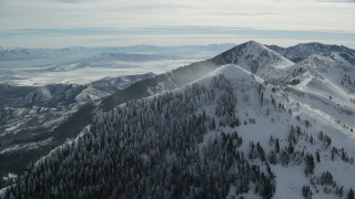 AX125_201 - 6K stock footage aerial video approach snowdrift blowing over trees on a mountain peak slope, Oquirrh Mountains, Utah