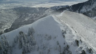 AX125_202 - 6K stock footage aerial video orbit mountain summit with snowdrifts in wintertime in Oquirrh Mountains, Utah