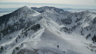 AX125_203 - 6K stock footage aerial video of flying over a mountain ridge with snowdrifts, approach Lowe Peak in winter, Utah