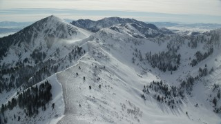 AX125_204 - 6K stock footage aerial video fly over snowy mountain ridge and pan to snowdrifts and Lowe Peak, Utah