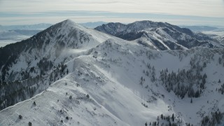 AX125_205 - 6K stock footage aerial video of snowdrifts on mountain near Lowe Peak in winter, Oquirrh Mountains, Utah