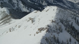 AX125_209 - 6K stock footage aerial video orbit snowy summit of Rocky Peak in wintertime, Oquirrh Mountains, Utah