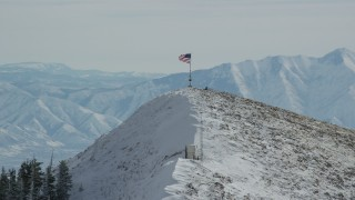 AX125_210 - 6K stock footage aerial video approach American flag waving atop a snowy peak in winter, Oquirrh Mountains, Utah