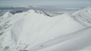 AX125_212 - 6K stock footage aerial video of snowy slopes in the Oquirrh Mountains of Utah in winter