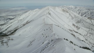 AX125_214 - 6K stock footage aerial video fly over snowy ridge in Utah's Oquirrh Mountains in wintertime