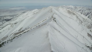 AX125_215 - 6K stock footage aerial video of flying over a wintery ridge in the Oquirrh Mountains of Utah