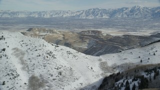 AX125_226 - 6K stock footage aerial video orbit Bingham Canyon Mine beyond snowy mountain ridge in winter, Utah