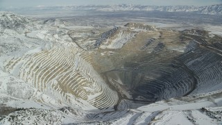 AX125_229 - 6K stock footage aerial video orbiting the Bingham Canyon Mine in winter with light snow in Utah