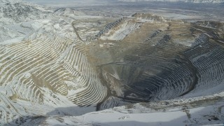 AX125_230 - 6K stock footage aerial video orbit rim of Bingham Canyon Mine in Utah with light winter snow
