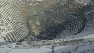 AX125_231 - 6K stock footage aerial video of the bottom of the Bingham Canyon Copper Mine with winter snow, Utah