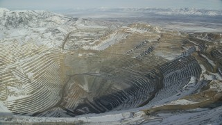 AX125_232 - 6K stock footage aerial video of orbiting Bingham Canyon Mine with light winter snow in Utah