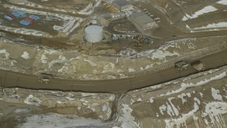 AX125_237 - 6K stock footage aerial video of orbiting gravel haulers in the Bingham Canyon Copper Mine in winter, Utah