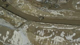 AX125_238 - 6K stock footage aerial video orbiting a group of gravel haulers at Bingham Canyon Mine in winter, Utah