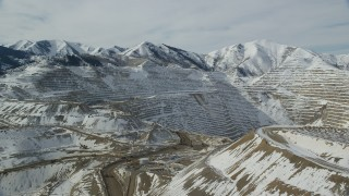 AX125_240 - 6K stock footage aerial video of orbiting the Bingham Canyon Mine in Utah with winter snow