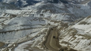 AX125_243 - 6K stock footage aerial video orbit Bingham Canyon Mine with gravel haulers and light snow, Utah