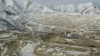 AX125_245 - 6K stock footage aerial video orbit the Bingham Canyon Mine and gravel haulers on a dirt road in winter, Utah