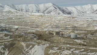 AX125_246 - 6K stock footage aerial video orbit Bingham Canyon Mine with gravel haulers on a dirt road in winter, Utah