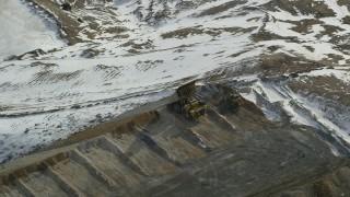 AX125_252 - 6K stock footage aerial video of gravel hauler dumping dirt and rocks at Bingham Canyon Mine, Utah, in winter