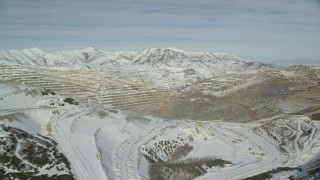 AX125_254 - 6K stock footage aerial video of Bingham Canyon Mine with winter snow in Utah