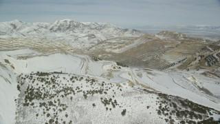 AX125_255 - 6K stock footage aerial video orbit snowy perimeter of the Bingham Canyon Mine in winter, Utah