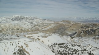 AX125_256 - 6K stock footage aerial video of a view across the Bingham Canyon Copper Mine with winter snow, Utah