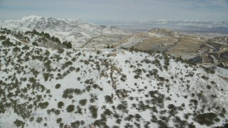 AX125_257 - 6K stock footage aerial video flyby snowy mountain to reveal the Bingham Canyon Mine in winter, Utah