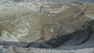 AX125_263 - 6K stock footage aerial video fly over deep open pit copper mine with winter snow, Bingham Canyon Mine, Utah