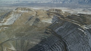 AX125_264 - 6K stock footage aerial video of orbiting the sides of the Bingham Canyon Mine with light snow, Utah