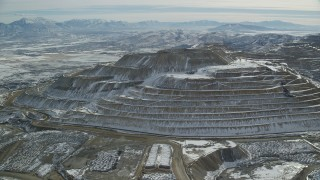 AX125_270 - 6K stock footage aerial video of tiered hill with winter snow at the Bingham Canyon Mine, Utah