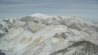 AX125_271 - 6K stock footage aerial video orbit an open pit mine with winter snow in the Oquirrh Mountains, Utah