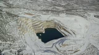 AX125_275 - 6K stock footage aerial video approach open pit mIne filled with water and tilt down in winter, Oquirrh Mountains, Utah