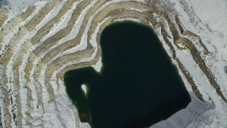 AX125_277 - 6K stock footage aerial video tilt to a bird's eye view of an open pit mine filled with water in winter, Oquirrh Mountains, Utah
