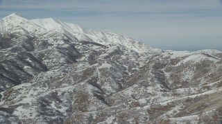 AX125_284 - 6K stock footage aerial video of flying by mountains with light snow near larger white peaks in winter, Oquirrh Mountains, Utah