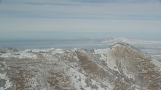 AX125_286 - 6K stock footage aerial video of Great Salt Lake seen from a snowy ridge in the Oquirrh Mountains, Utah