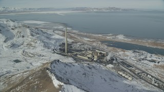 AX125_295 - 6K stock footage aerial video of Kennecott Smokestack and factory buildings with winter snow in Magna, Utah