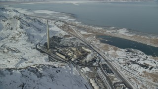 AX125_296 - 6K stock footage aerial video orbit factory buildings and Kennecott Smokestack with winter snow in Magna, Utah