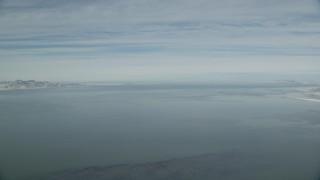 AX125_303 - 6K stock footage aerial video pan across the wide Great Salt Lake in winter, Utah
