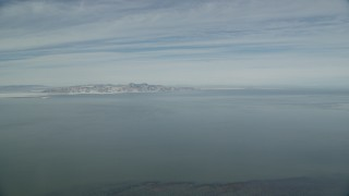 AX125_304 - 6K stock footage aerial video of the Great Salt Lake with winter ice and snow mountains on the shore, Utah