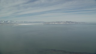 AX125_305 - 6K stock footage aerial video pan across the Great Salt Lake with winter ice and snowy shores, Utah