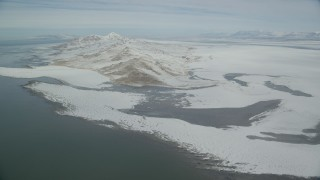 AX125_311 - 6K stock footage aerial video approach snowy mountains on the shore of Antelope Island, Utah