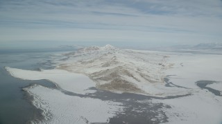 AX125_312 - 6K stock footage aerial video slow approach to snow mountains on Antelope Island, Utah